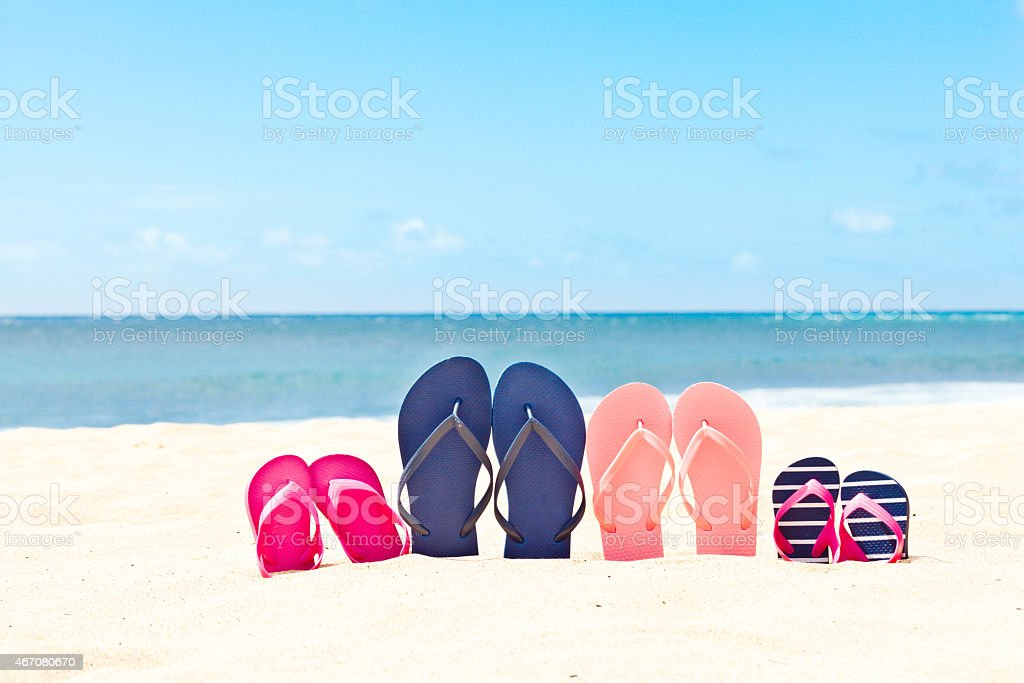 Family Beach Summer Vacation with Flip-flops in Sand by Sea stock photo