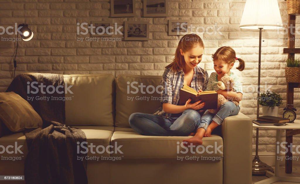 Família antes de ir para a mãe de cama lê ao seu livro de filha de criança perto de uma lâmpada à noite - foto de acervo