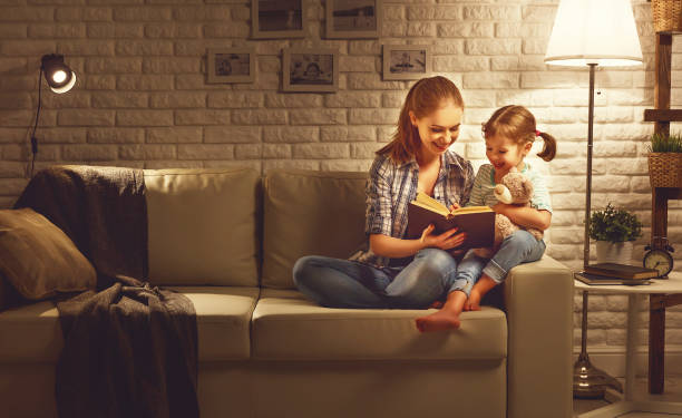 family before going to bed mother reads to her child daughter book near a lamp in the evening - family room stock photos and pictures