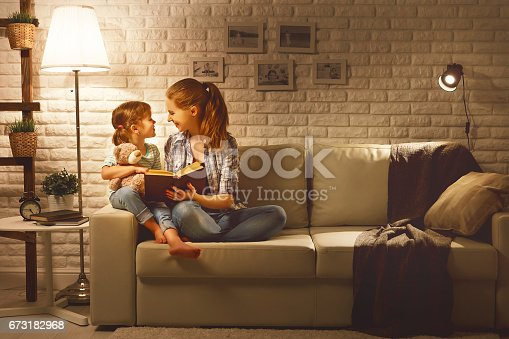 istock Family before going to bed mother reads to her child daughter book near a lamp in the evening 673182968