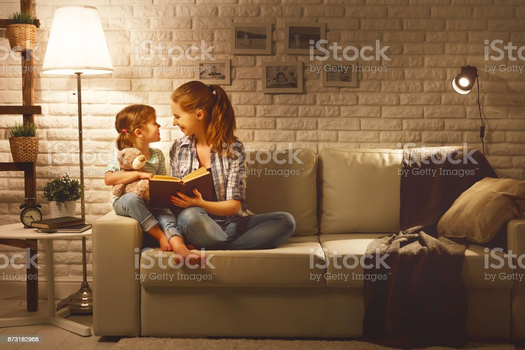 Family before going to bed mother reads to her child daughter book near a lamp in the evening bildbanksfoto