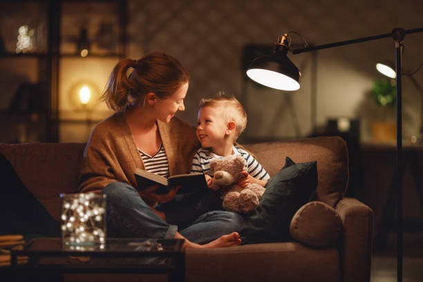 family before going to bed mother reads to her child son book near a lamp in the evening - light foto e immagini stock