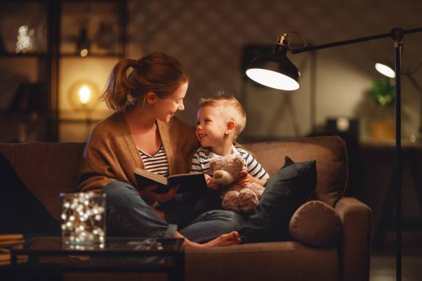 familj innan du går till sängs mamma läser till hennes barn son bok nära en lampa på kvällen - ljus bildbanksfoton och bilder