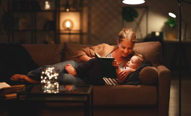Familie vor dem Schlafengehen Mutter liest ihrem Sohn Buch in der Nähe einer Lampe am Abend – Foto