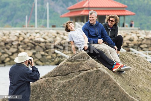 Family (two mature heterosexual parents and a preteen girl) being photographed during vacations by senior citizen.