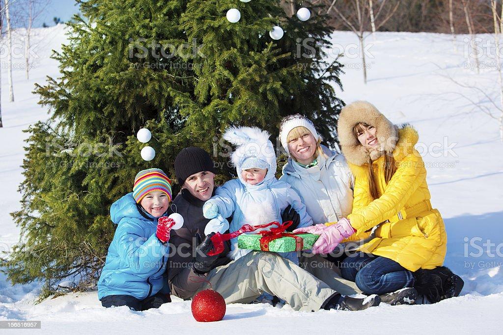 Family beside Christmas tree royalty-free stock photo