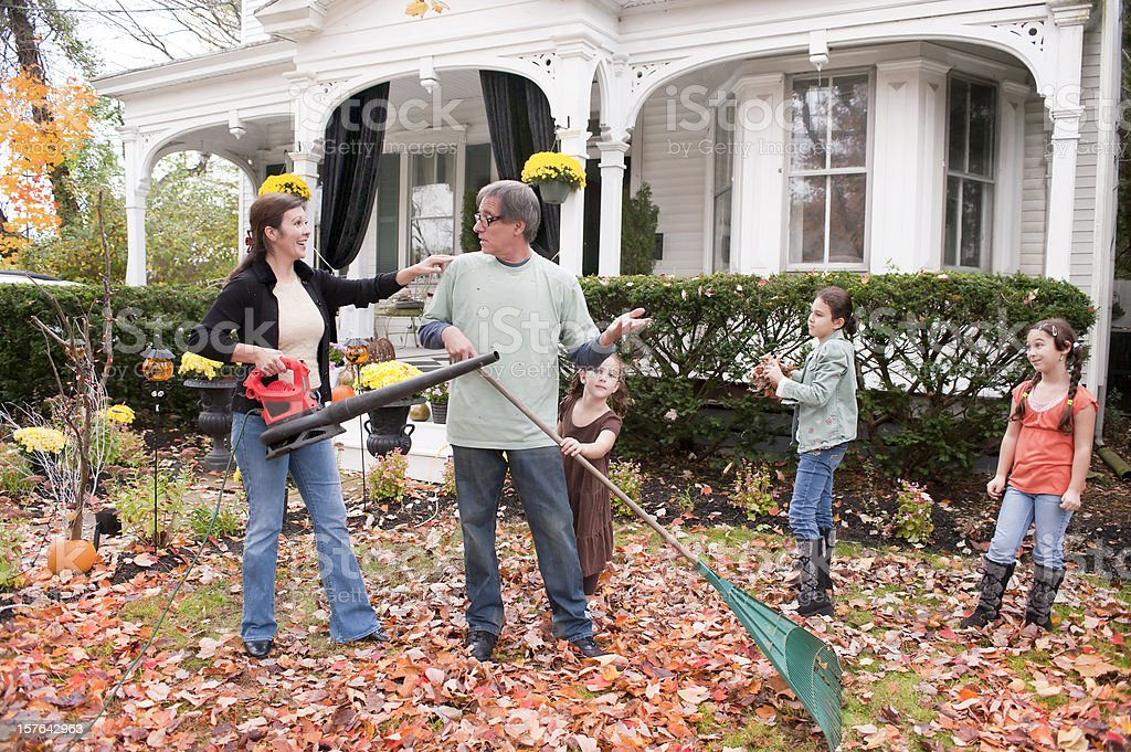 family blowing and raking leaves royalty-free stock photo