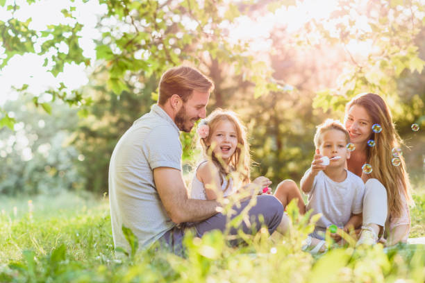 family blowing bubbles and laughing - mãe criança brincar relva efeito de refração de luz imagens e fotografias de stock