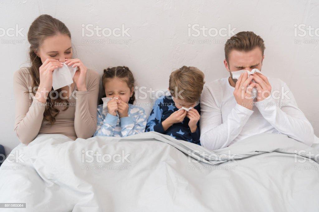 familia soplar narices en servilletas - foto de stock
