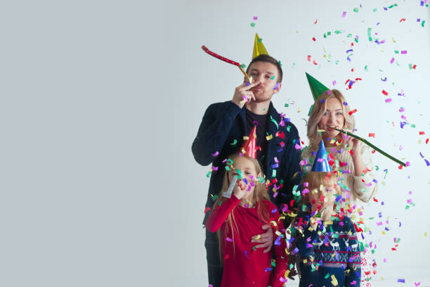 Family blowing party trumpets with confetti stock photo