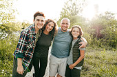 istock Family bonding and having a fun time together. Siblings and parents embracing and smiling at the camera. 1271545402