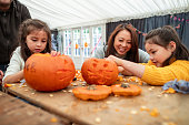 Mother and her daughters carving pumpkins together at a farm after picking them in preparation for Halloween.