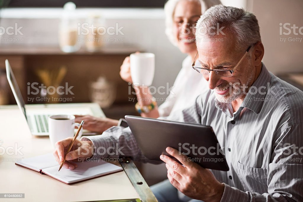 Family breakfast of elderly couple in the kitchen Real joy. Man surfing through Internet while woman drinking coffee and smiling at him Adult Stock Photo