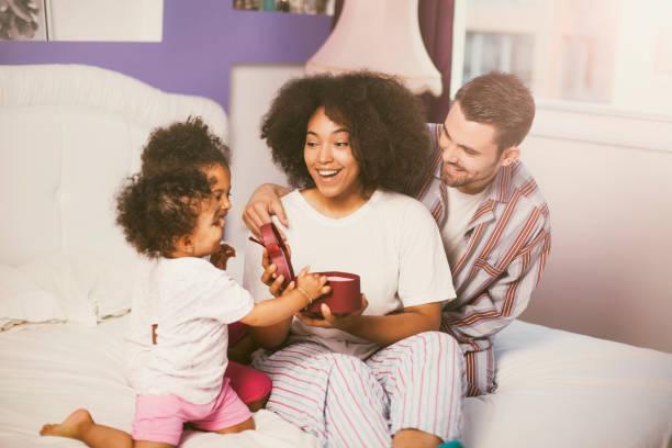 familie ihr mutter präsentiert im bett - marvel schlafzimmer stock-fotos und bilder