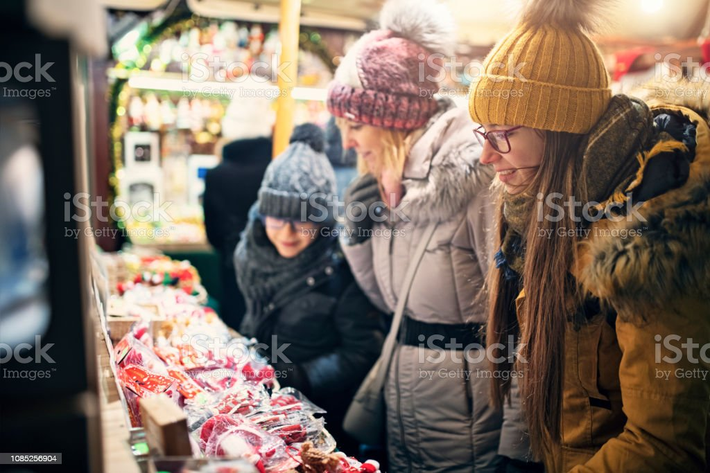 Family Browsing Christmas Decorations On Christmas Market