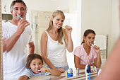 Family Brushing Teeth In Bathroom Mirror All Together