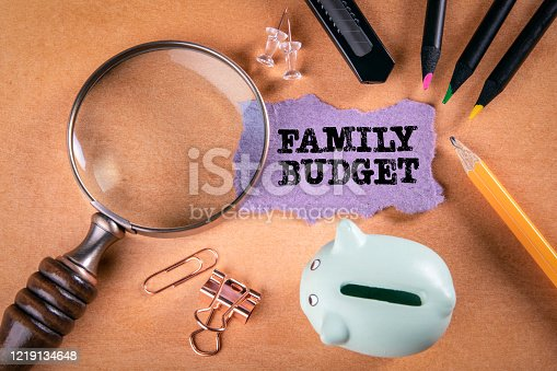 Family Budget. Savings, payments, planning and credit liabilities concept. Magnifying glass, stationery and note paper on the table