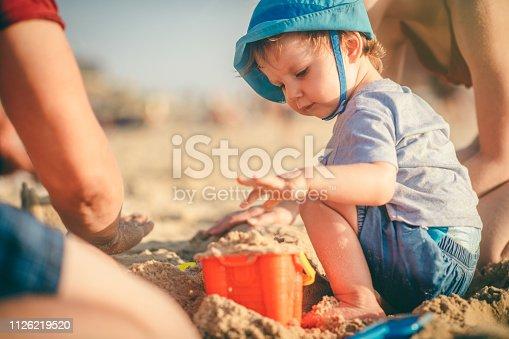 509423868 istock photo Family building a sandcastle on the beach near the sea 1126219520