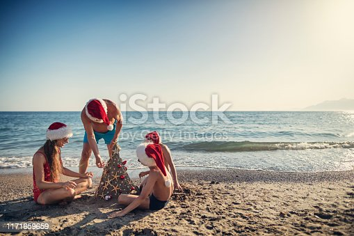 Father and kids are having fun during summer Christmas. Family wearing Santa hats is building and decorating a sand Christmas tree. Nikon D850