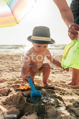 509423868 istock photo Family building sandcastle on the beach on summer holidays 1158407735