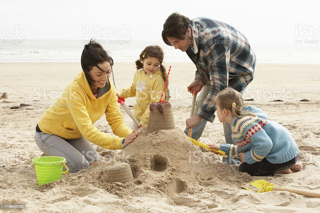 Family Building Sandcastle On Winter Beach royalty-free stock photo