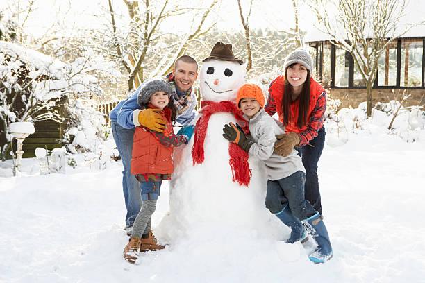 familie gebäude schneemann im garten - schneemann bauen stock-fotos und bilder
