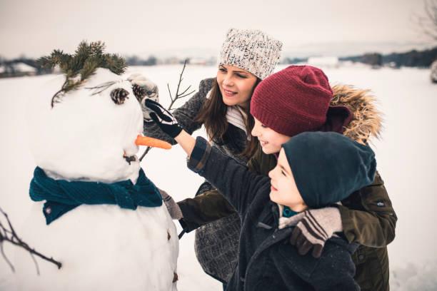 gebäude der familie schneemann - schneemann bauen stock-fotos und bilder