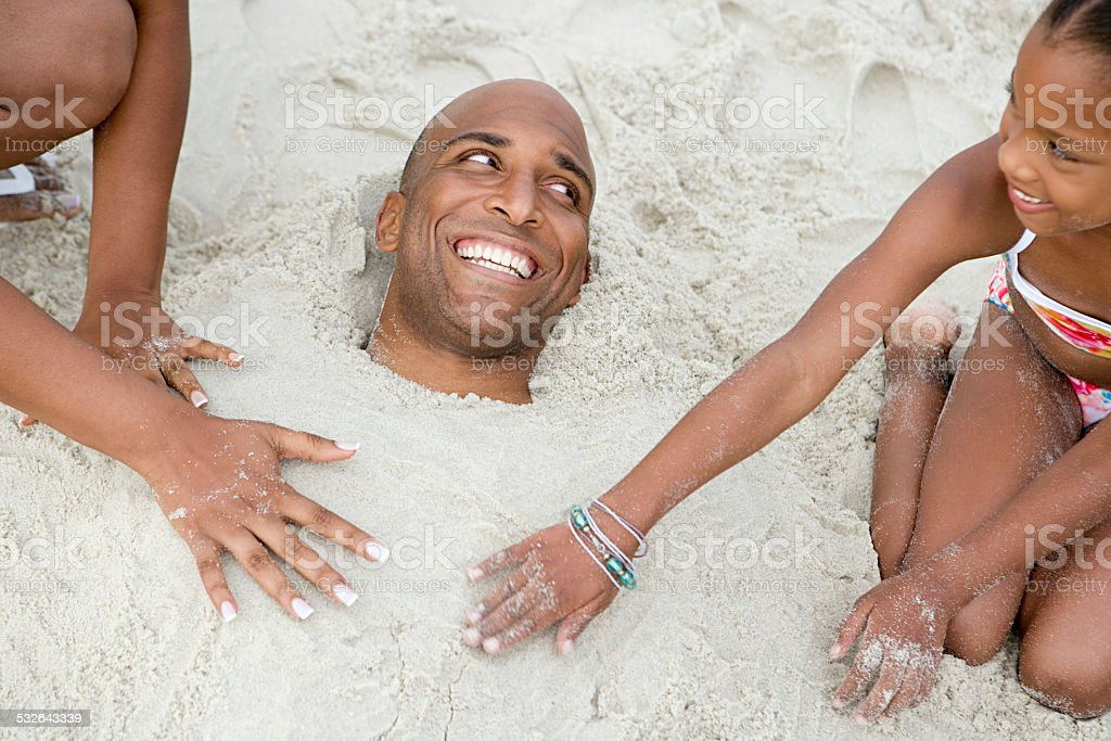 Family burying father in sand stock photo
