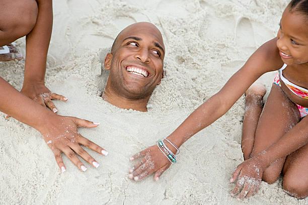 family burying father in sand - gömülü stok fotoğraflar ve resimler