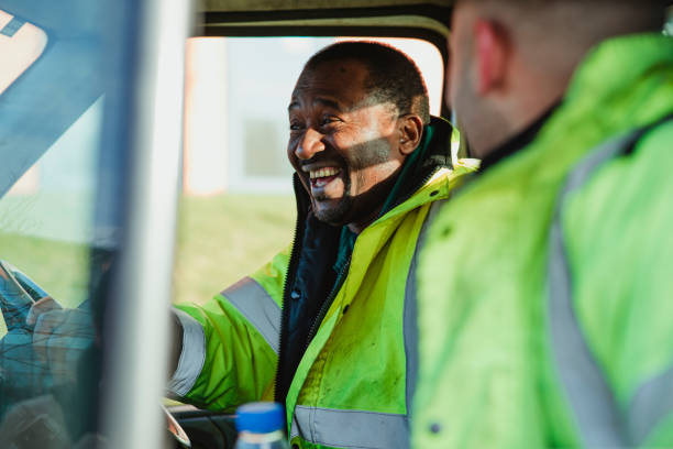 Family Business Fun Senior man and his son are laughing and talking together in their work van. reflective clothing stock pictures, royalty-free photos & images