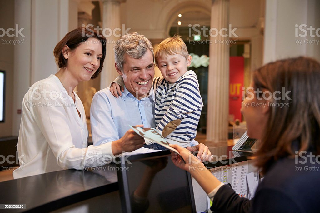 Family Buying Entry Tickets To Museum From Reception stock photo