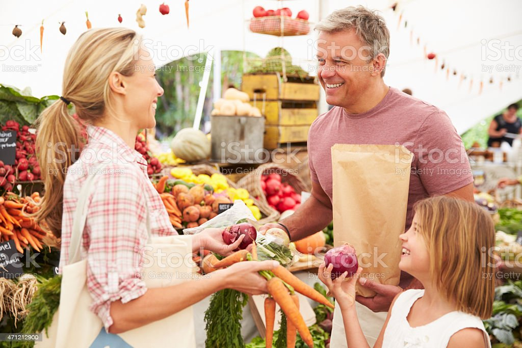 Family Buying Fresh Vegetables At Farmers Market Stall stock photo