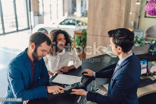 Young family in the showroom paying with credit card for buying new car