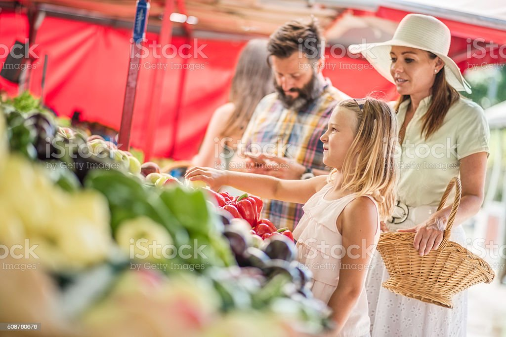 Family buying vegetables on outdoor stand stock photo