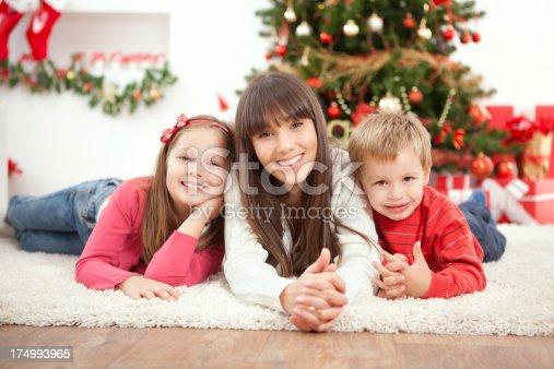 172407626istockphoto Family by christmas tree. 174993965