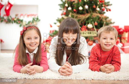 172407626istockphoto Family by christmas tree. 175209702