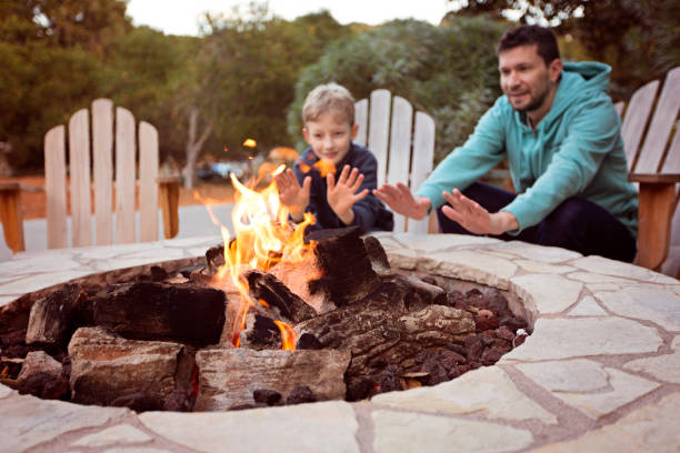 family by firepit view of firepit and happy smiling family of two, father and son, warming their hands by the fire and enjoying time together in the background family bbq stock pictures, royalty-free photos & images