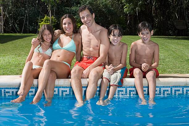 Family by swimming pool stock photo