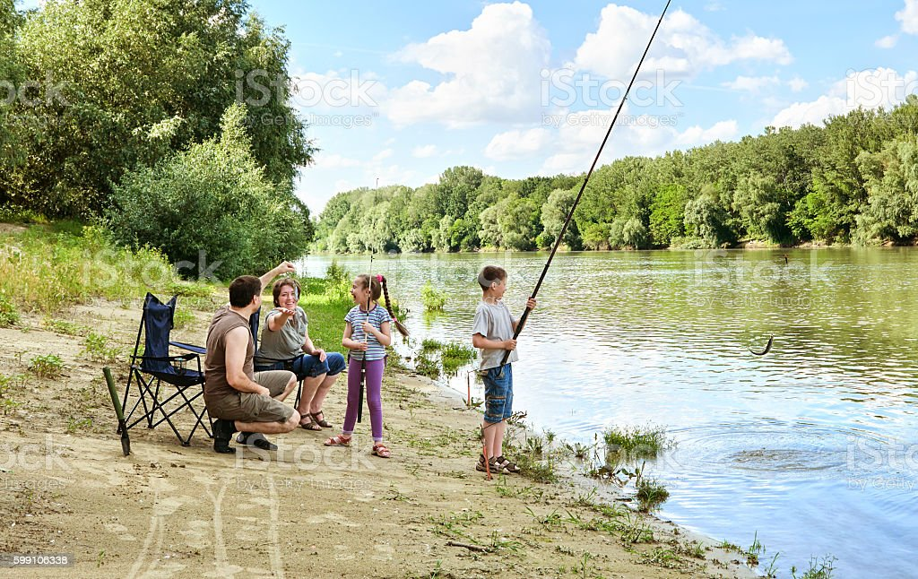 family camping and fishing, people active nature, child caught fish stock photo