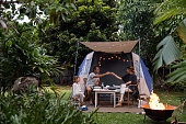 Real life Aussie parents cheers over a glass of red wine while camping in their backyard
