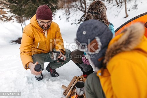 Family relaxing with coffee near campfire after hiking on snow covered landscape