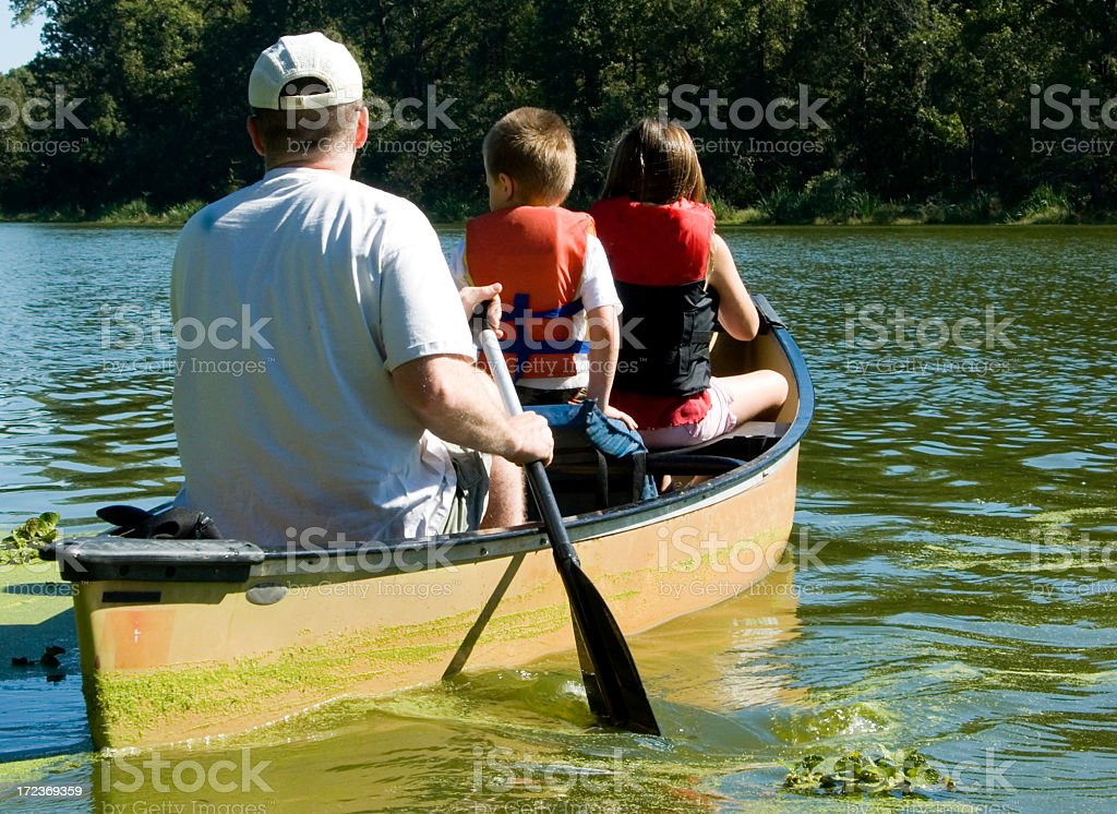 Family Camping Vacation, Dad and kids paddling a canoe royalty-free stock photo