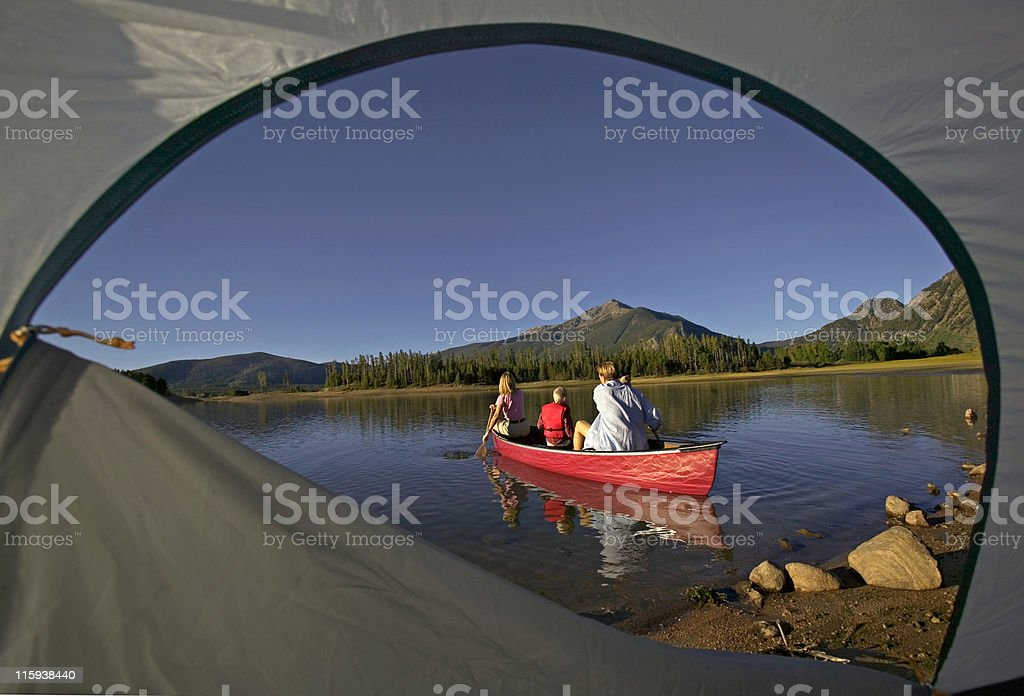 A family canoeing on a mountain lake, as seen out of a tent royalty-free stock photo
