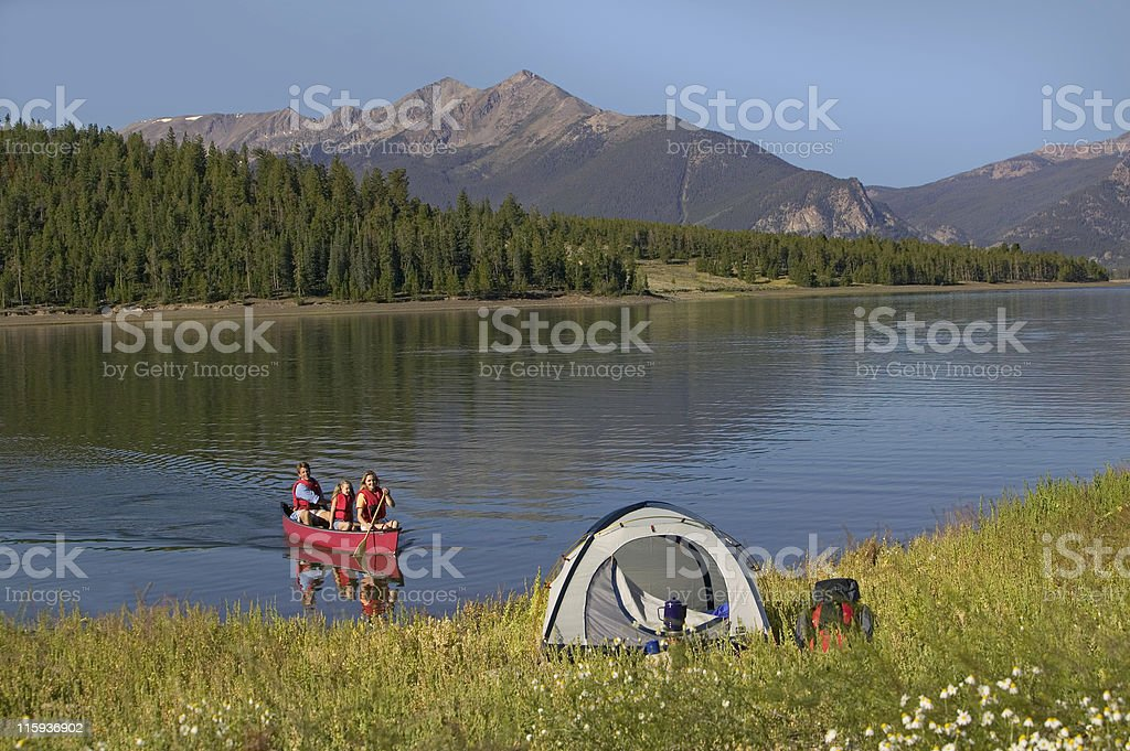 Family Canoeing on Mountain Lake  by Tent royalty-free stock photo