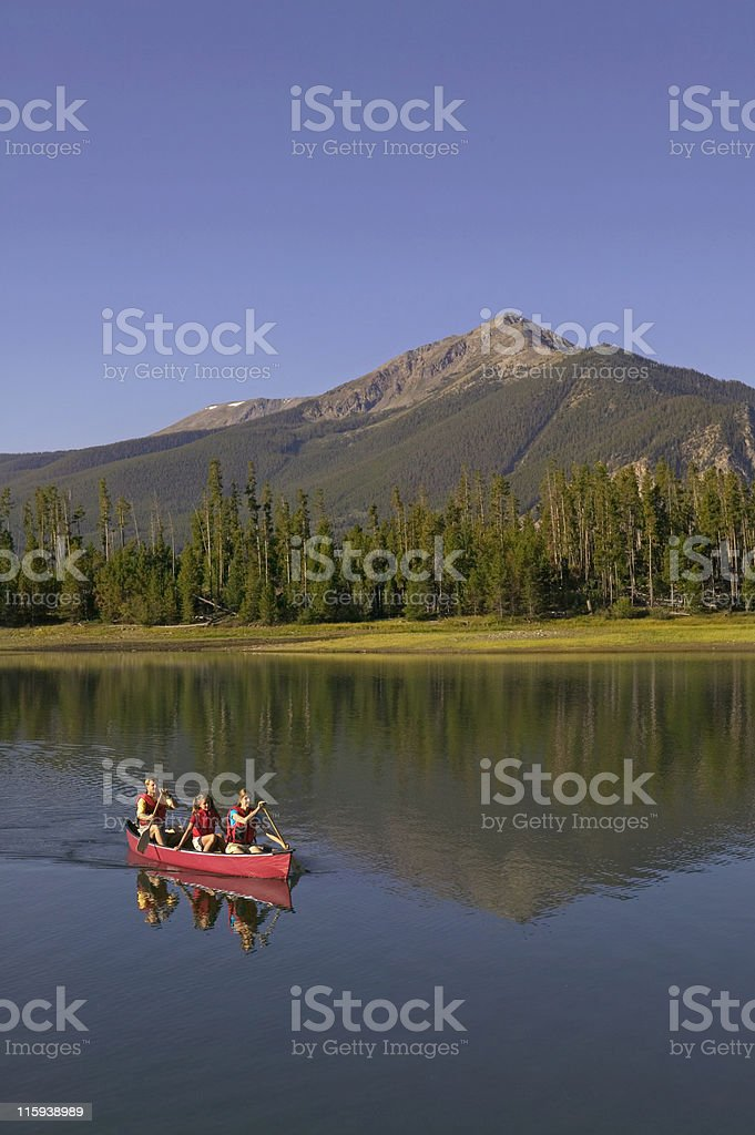 Family Canoeing on Mountain with Reflection royalty-free stock photo