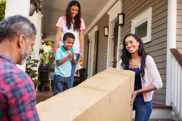 family carrying big box purchase into house - furniture shopping stock photos and pictures