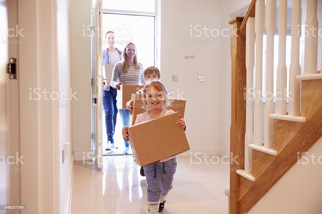 Family Carrying Boxes Into New Home On Moving Day Family Carrying Boxes Into New Home On Moving Day Moving House Stock Photo