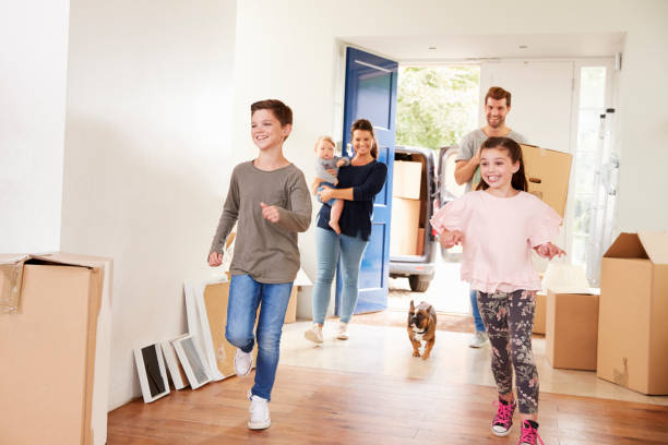 family carrying boxes into new home on moving day - house hunting stock photos and pictures