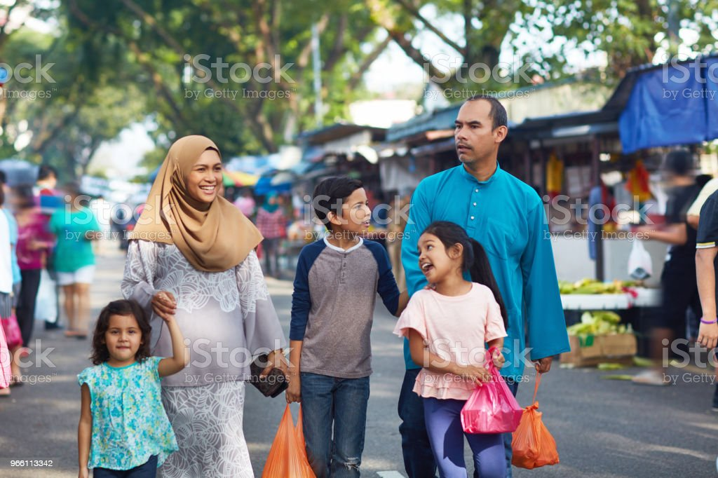 Family carrying plastic bags walking in market - Royalty-free 10-11 Years Stock Photo