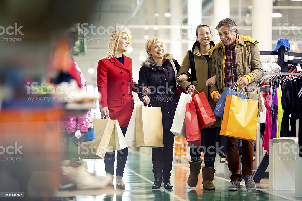 Family carrying shopping bags in mall stock photo